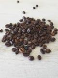 Grillade kaffebönor på en tabell Arkivbild