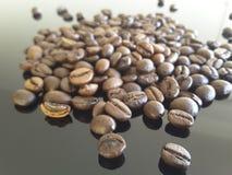 Grillade kaffebönor på en tabell Royaltyfri Foto