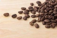 Grillade kaffebönor på wood bakgrund Arkivbild
