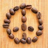 Grillade kaffebönor som är ordnade i fredtecknet för bakgrunder, bakgrunder och baner Royaltyfria Foton