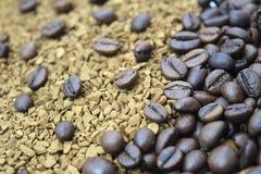 Grillade kaffebönor som över tippas på vitt exponeringsglas arkivbild