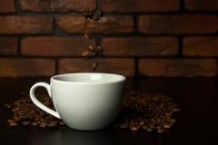 Grillade kaffebönor som faller in i koppen Arkivfoton