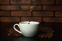 Grillade kaffebönor som faller in i koppen Arkivbild