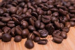 Grillade kaffebönor tätt upp/makrosikt på naturlig träbakgrund royaltyfria bilder