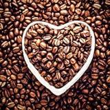 Grillade kaffebönor i en formad hjärta bowlar på Valentine Day Ho Arkivbilder
