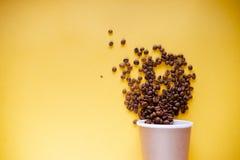 Grillade kaffekorn och bästa sikt för takeaway kopp Koppen för hantverkpapperste på orange bakgrundslägenhet lägger Kaférengöring royaltyfria foton