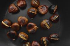 Grillade kastanjer i en gjutjärnkastrull på en trätabell arkivfoto
