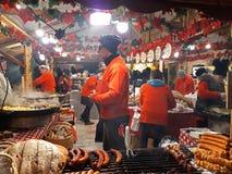 Grillade korvar för folk marknadsför småfisk på stort hängande galler på jul Royaltyfri Foto