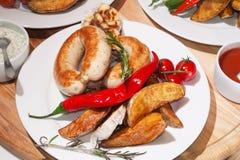 Grillade korvar med bakade potatisar, körsbärsröda tomater och örter Arkivbild