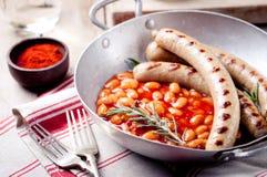 Grillade korvar med bönor i tomatsås Arkivfoto