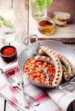Grillade korvar med bönor i tomatsås Arkivbild
