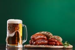 Grillade korvar med exponeringsglas av öl Royaltyfria Foton