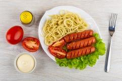 Grillade korvar med spagetti, grönsallat i plattan, peppar, mayon royaltyfria foton
