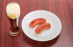 Grillade korvar på en vitt maträtt och exponeringsglas av öl Royaltyfri Bild