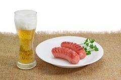 Grillade korvar på en vitt maträtt och exponeringsglas av öl Arkivbild