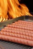 Grillade korvar på stekpannan och BBQ grillar i bakgrund, XXXL Arkivfoto
