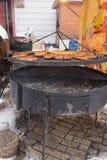 Grillade korvar som håller som är varma på ett galler Arkivfoto