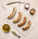 Grillade korvar som ligger på tappningskärbräda med rosmarin, kryddor, currysås och kött, dela sig på bästa sikt för lantlig bakg Arkivbild