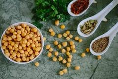 Grillade kryddiga kikärtar på grön bakgrund, bästa sikt Arkivbild