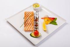 Grillade lax och grönsaker på den vita plattan royaltyfri fotografi
