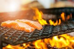 Grillade laxbiffar på ett galler Brandflammagaller Restaurang- och trädgårdkök Trädgårds- parti Sund maträtt royaltyfri bild