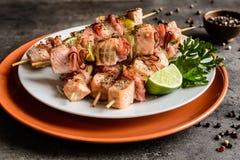 Grillade laxsteknålar med bacon och limefrukt arkivbilder