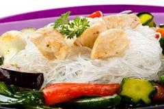Grillade meat, ricenudlar och grönsaker på white Royaltyfri Foto