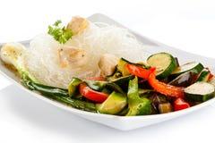Grillade meat, ricenudlar och grönsaker på white Royaltyfri Bild