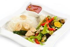 Grillade meat, ricenudlar och grönsaker på white Arkivbild
