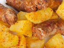 Grillade meatkorvar med potatisar Fotografering för Bildbyråer