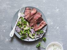 Grillade nötköttbiff och gröna ärtor, rädisa, gurkasallad på en grå bakgrund, bästa sikt Arkivbild