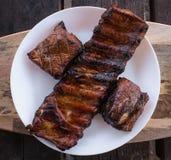 Grillade och rökte grillade grisköttstöd på en vit platta arkivbild
