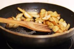 Grillade potatisar tätt upp i en doftande smaktillsats i panna i smör med träskeden arkivfoto