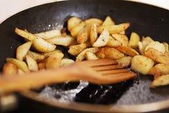 Grillade potatisar tätt upp i en doftande smaktillsats i panna i smör med träskeden royaltyfria bilder