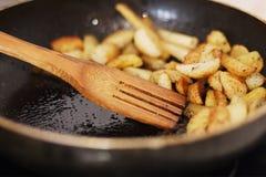 Grillade potatisar tätt upp i en doftande smaktillsats i panna i smör med träskeden fotografering för bildbyråer
