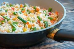 Grillade ris med grönsaker i en keramisk panna med ett litet belopp av olja fotografering för bildbyråer