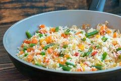 Grillade ris med grönsaker i en keramisk panna med ett litet belopp av olja arkivbilder