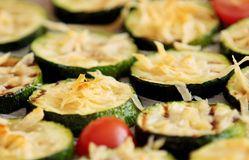 Grillade skivor av zucchinin med parmesanost och körsbärsröda tomater Slapp fokus Arkivfoto