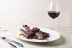 Grillade stöd tjänade som över den stora vita plattan med ett exponeringsglas av rött vin arkivfoto