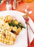 Grillade tioarmad bläckfisk och stekt potatis på en platta Royaltyfri Fotografi