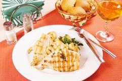 Grillade tioarmad bläckfisk och stekt potatis på en stor platta Arkivbild