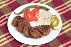 Grillade turkiska köttbullar, (Kofte), på den vita plattan Arkivbilder