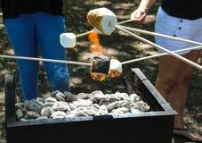 Grillage des guimauves sur le gril de BBQ au parc Images libres de droits