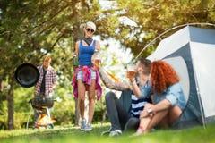 Grillage masculin et femelle avec des verres de bière avec la fille au camp Photos stock