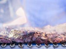 Grillant la viande rouge et les saucisses au coucher du soleil recueillant dehors avec Photo libre de droits