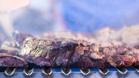 Grillant la viande rouge et les saucisses au coucher du soleil recueillant dehors avec Photographie stock libre de droits