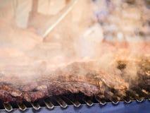 Grillant la viande rouge et les saucisses au coucher du soleil recueillant dehors avec Photos stock