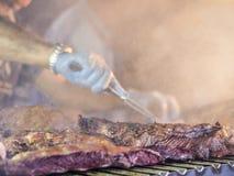 Grillant la viande rouge et les saucisses au coucher du soleil recueillant dehors avec Photographie stock