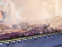 Grillant la viande rouge et les saucisses au coucher du soleil recueillant dehors avec Images libres de droits