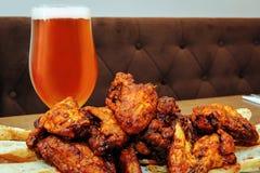 Grillat fega vingar och exponeringsglas av öl Arkivfoton